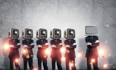 Businessmen in suits with old TV instead of their heads keeping arms crossed while standing in a row and one at the head with laptop in empty room against gray wall on background.