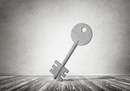 Key stone figure as symbol of access in empty concrete room Stock Photo