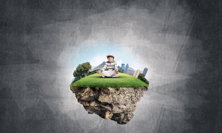 Young little boy keeping eyes closed and looking concentrated while meditating on flying island in the air with gray dark wall on background. 3D rendering. Stock Photo