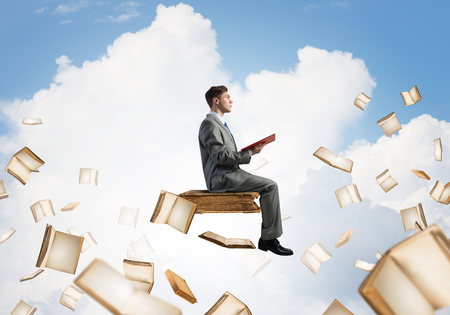 Young businessman floating in blue sky with red book in hands Banque d'images