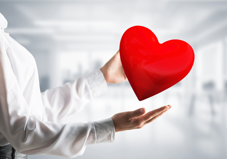Cropped image of business woman in shirt keeping big red heart in his hands with office view on background. Mixed media.