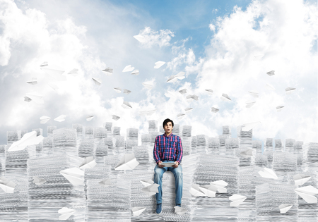 Young man in casual clothing sitting on pile of documents among flying paper planes with cloudly skyscape on background. Mixed media.