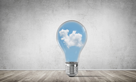 Glass lightbulb with clouds inside in empty room with grey wall on background. 3D rendering.