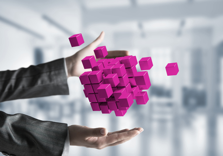 Closeup shot of business woman hands holding multiple violet cubes in hands with office view background. Mixed media. Stock Photo