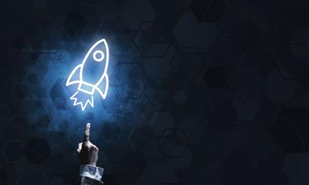 Mans hand pointing to light rocket on dark background Stock Photo