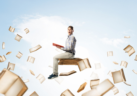 Jeune homme choqué flottant dans le ciel bleu avec un livre rouge dans les mains Banque d'images - 92360357