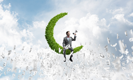 Young businessman sitting on green moon and screaming emotionally in megaphone Stock Photo