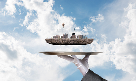 Cropped image of waitresss hand in white glove presenting modern city block on metal tray with blue cloudy skyscape on background. 3D rendering.