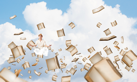 Man in white clothing keeping eyes closed and looking concentrated while meditating among flying books in the air with cloudy skyscape on background.