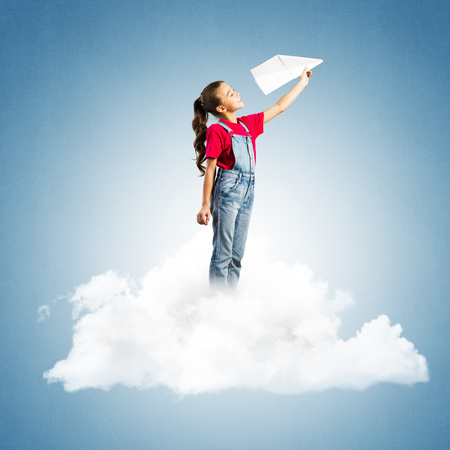 Cute kid girl standing on cloud and throwing paper plane Banco de Imagens