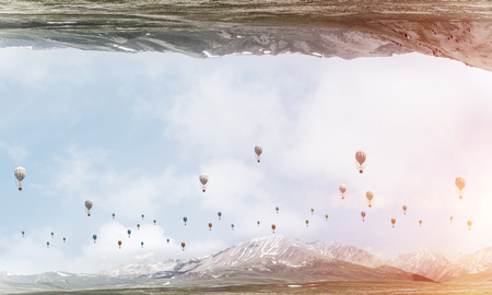Abstract image of two nature worlds located upside down to each other with flying aerostats on sky background. Wallpaper, backdrop with copyspace.