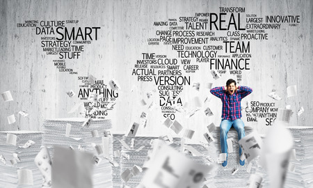 Young man in casual wear sitting among flying documents with business-related terms in form of world map on background. Mixed media. Stock Photo