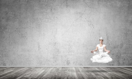 Young woman keeping eyes closed and looking concentrated while meditating on cloud in the air with gray concrete wall on background.