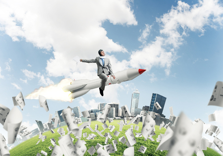 Conceptual image of young businessman in suit flying on rocket among flying papers with cityscape and blue sky on background.