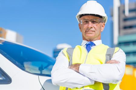 胸に腕を組んだハードハットの自信ある建設エンジニア