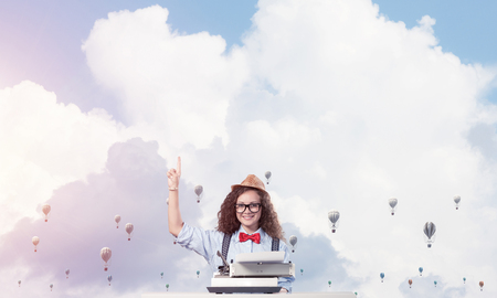 Young and beautiful woman writer in hat and eyeglasses using typing machine and pointing upside while sitting at the table with flying aerostats and cloudy skyscape on background.