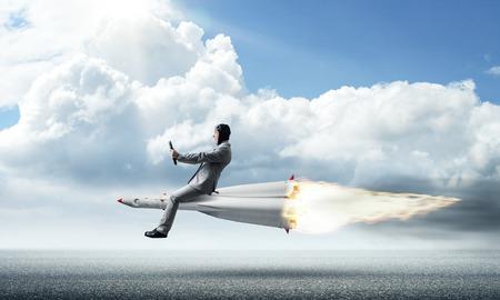 背景に青い曇り空とアスファルトの道路の上のロケットの飛行スーツの青年実業家のイメージ。 写真素材