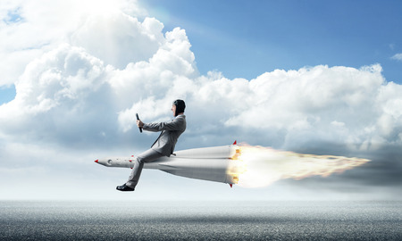 Conceptual image of young businessman in suit flying on rocket above asphalt road with blue cloudy sky on background. Banco de Imagens
