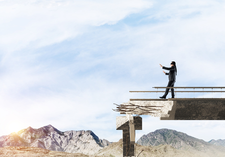 Businessman walking blindfolded on concrete bridge with huge gap as symbol of hidden threats and risks. Skyscape and nature view on background. 3D rendering. 写真素材