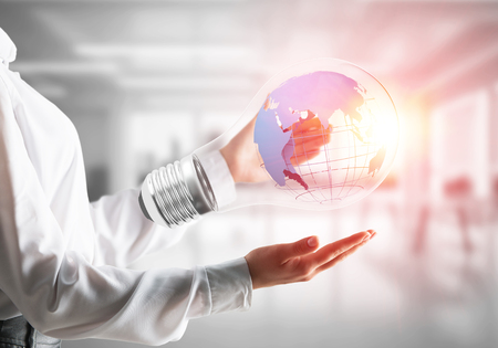 Cropped image of businessman in shirt holding lightbulb with Earth globe inside in his hands. Sunlight on office view background.