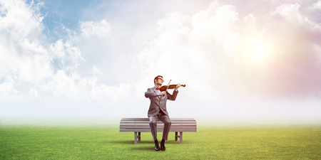 Young man wearing suit and glasses sitting on bench and playing violin Stock Photo