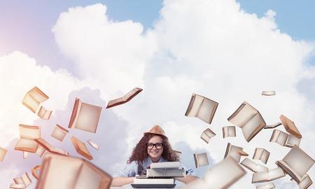 Escritor joven y hermosa de la mujer en sombrero y lentes usando la máquina de escribir mientras que se sienta en la tabla entre los libros de vuelo con skyscape nublado en fondo.