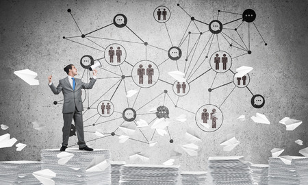 Businessman with speaker in hand standing among flying paper planes with social network structure on background. Mixed media.