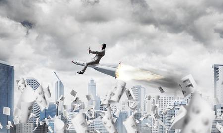 Conceptueel beeld van jonge en gelukkige zakenman in pak die op raket onder vliegende documenten met moderne cityscape met wolkenkrabbers en blauwe hemel op achtergrond vliegen.