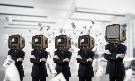 Businessmen in suits with old TV instead of their heads keeping arms crossed while standing in a row among flying paper documents inside office building.