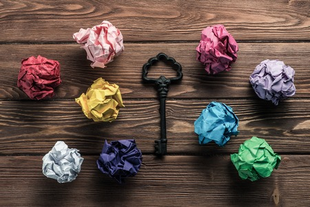 Set of multiple colorful crampled paper ball and key among them, placed on wooden table as means of searching of new ideas. Reklamní fotografie