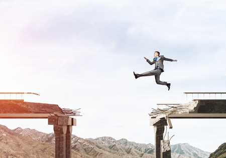 Businessman jumping over huge gap in concrete bridge as symbol of overcoming challenges. Skyscape and nature view on background. 3D rendering. Stock Photo