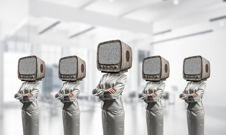 Business women in suits with old TV instead of their heads keeping arms crossed while standing in a row inside office building.
