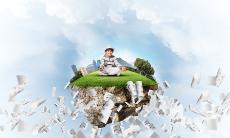 Young little boy keeping eyes closed and looking concentrated while meditating on flying island among flying papers with cloudy skyscape on background. 3D rendering. Stock Photo