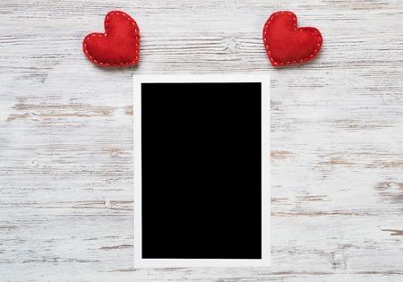 Leerer Fotorahmen und Liebesherzen auf Holztisch Standard-Bild - 93126069