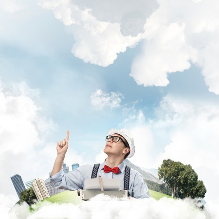 Young man writer in hat and eyeglasses using typing machine and pointing upside while sitting at the table with floating city and cloudy skyscape on background. Stock Photo