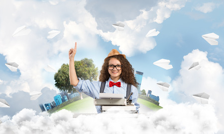 Young woman writer in hat and eyeglasses using typing machine and pointing upside while sitting at the table among flying paper planes with floating city island and cloudy skyscape on background.