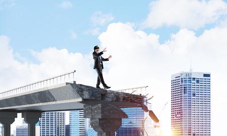 隠れた脅威とリスクの象徴として巨大なギャップを持つコンクリート橋の上を目隠し歩くビジネスマン。背景の都市景観ビュー。3D レンダリング。 写真素材