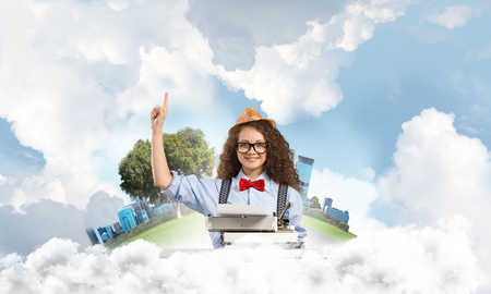 Young and beautiful woman writer in hat and eyeglasses using typing machine and pointing upside while sitting at the table with floating city island and cloudy skyscape on background.