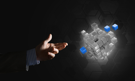 Close of businessman hand holding cube figure as symbol of innovation, mixed media Stock Photo