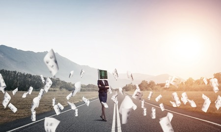 Business woman in suit with monitor instead of head keeping arms crossed while standing on the road among flying papers with beautiful landscape on background. Stock Photo
