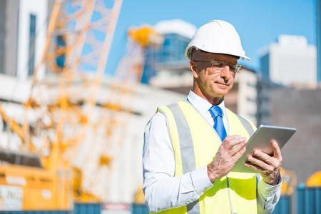Senior engineer man in suit and helmet working on tablet pc Foto de archivo