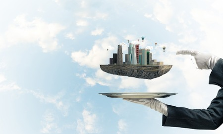 Cropped image of waitresss hand in white glove presenting modern city block on metal tray and pointing on it with blue cloudy skyscape on background. 3D rendering. Stock Photo