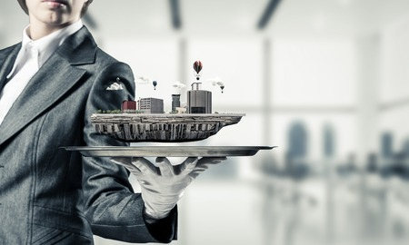 Cropped image of waitresss hand in white glove presenting modern city block on metal tray with office view on background. 3D rendering.