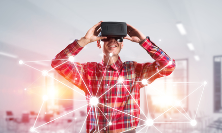 Young man with virtual reality headset or 3d glasses over connection background. Mixed media 版權商用圖片