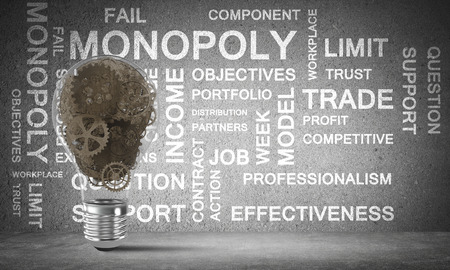 Glass lightbulb with multiple gears inside placed against business related terms on grey wall on background. 3D rendering. Stock Photo