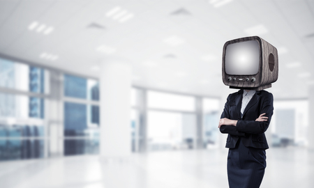 Cropped image of business woman in suit with old TV instead of head keeping arms crossed while standing inside office building.