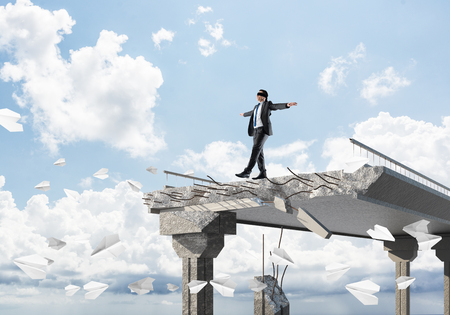 Businessman walking blindfolded among flying paper planes on concrete bridge with huge gap as symbol of hidden threats and risks. Skyscape and nature view on background. 3D rendering. Stock Photo
