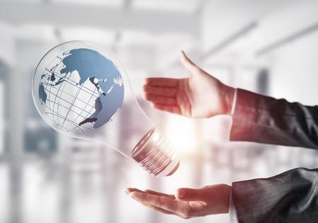 Imagem colhida das mãos da mulher de negócio que guardam a ampola com globo da terra para dentro. Luz solar no fundo da opinião de escritório. Foto de archivo