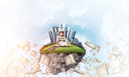 Young little boy keeping eyes closed and looking concentrated while meditating on flying island among flying books with cloudy skyscape on background. 3D rendering. Stock Photo