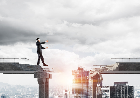 Businessman walking blindfolded on concrete bridge with huge gap as symbol of hidden threats and risks. Cityscape view with sunlight on background. 3D rendering. 写真素材